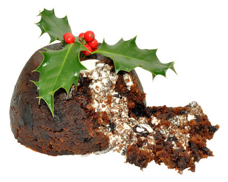Traditional Christmas pudding with holly leaves, red berries and cream, isolated on a white background.