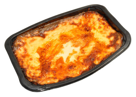bought: Cooked shop bought beef lasagne convenience meal in a black plastic tray, isolated on a white background. Stock Photo