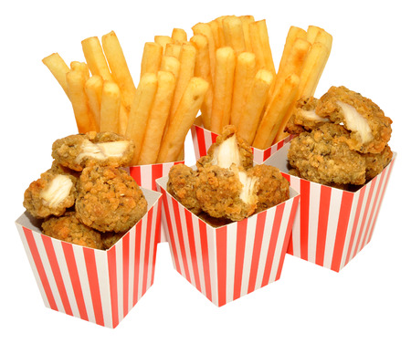 Southern fried chicken nuggets and French fries in red and white striped boxes, isolated on a white background. photo