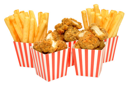 Southern fried chicken nuggets and French fries in red and white striped boxes, isolated on a white background. Archivio Fotografico