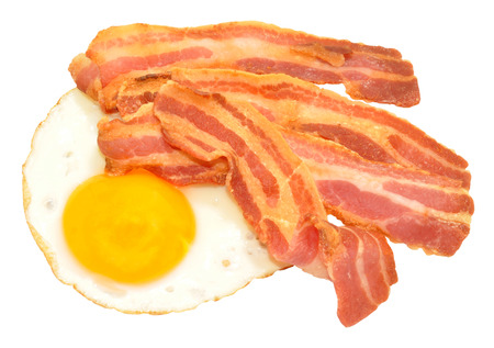 Fried egg and streaky bacon rashers isolated on a white background