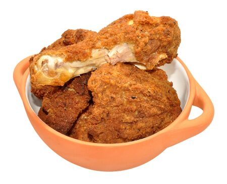 portions: Cooked southern fried chicken portions in a bowl isolated on a white background