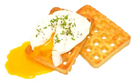 Single poached egg with runny yolk on potato waffles isolated on a white background photo