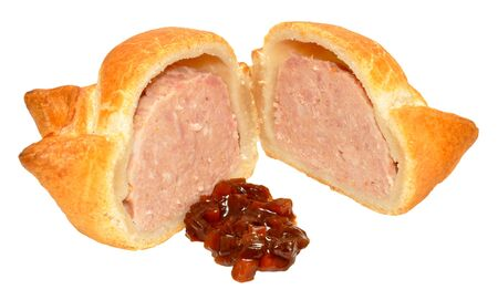 A single fresh crusty pork pie cut in half with chutney relish isolated on a white background photo