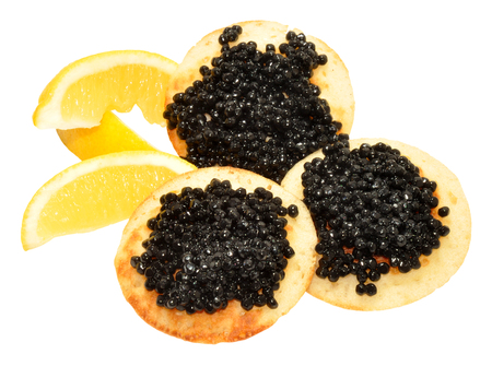 blini: Black caviar on small blini pancakes with lemon wedges isolated on a white background Stock Photo