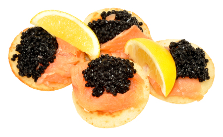blini: Salmon and caviar on small blini pancakes with lemon wedges isolated on a white background