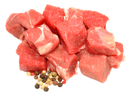 cubed: Fresh raw uncooked diced beef meat with peppercorns isolated on a white background