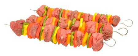 Raw beef and sweet pepper kebabs isolated on a white background photo