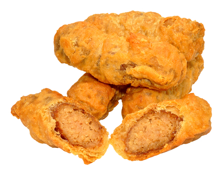 Crispy fried batter covered pork sausages isolated on a white background.