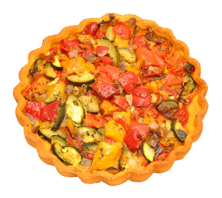 Freshly baked savoury vegetable flan filled with sweet peppers and courgette and isolated on a white background