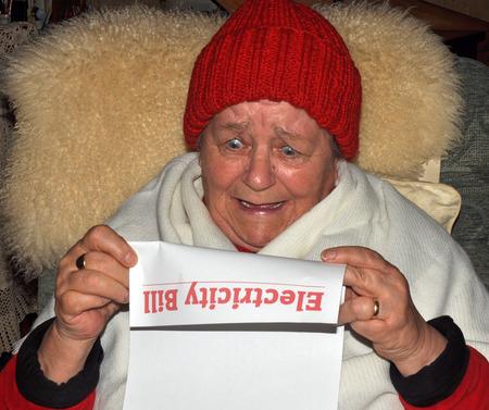 老婦人は押しながらショックを受けた式ユーティリティ法案を読みます。 写真素材