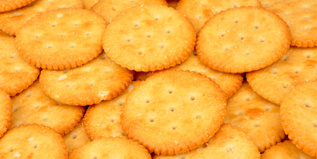 biscuits: Scattered round salty savoury cheese biscuits background Stock Photo