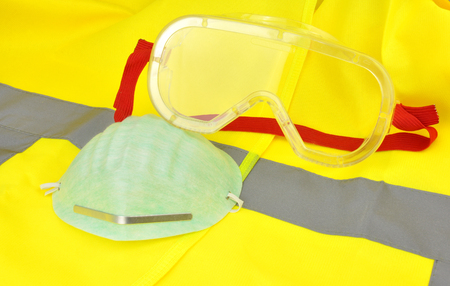 high visibility: Plastic industrial safety goggles with red elastic strap on a yellow high visibility vest Stock Photo