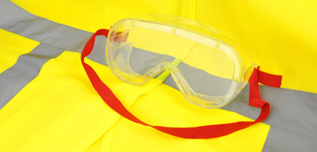 safety goggles: Plastic industrial safety goggles with red elastic strap on a yellow high visibility vest Stock Photo