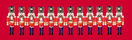 Twelve traditional wooden soldier drummer Christmas decorations on a red background Stock Photo