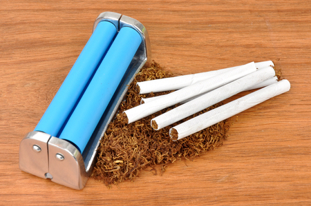 anti social: Cigarette rolling machine and tobacco on a wood background