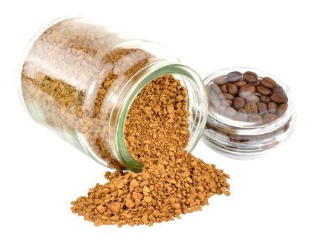 granules: Open jar of instant coffee with coffee granules spilling out isolated on a white background