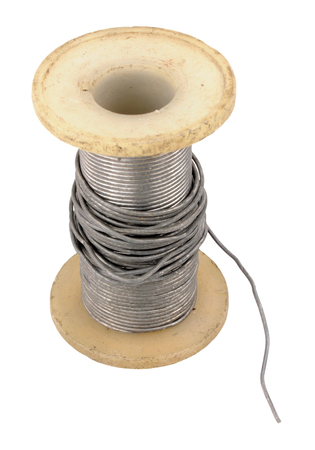solder: Spool of old electrical solder isolated on a white background