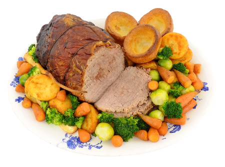 baked meat: Roast beef with Yorkshire puddings and mixed vegetables on a serving plate isolated on a white background