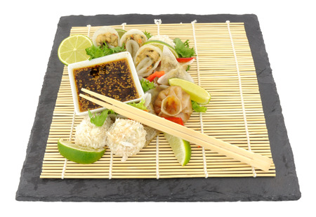 cantonese: Traditional Cantonese steamed dim sum snacks with soy sauce dip on a bamboo mat isolated on a white background