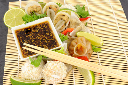 cantonese: Traditional Cantonese steamed dim sum snacks with soy sauce dip on a bamboo mat Stock Photo