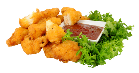 battered: Group of fried battered chicken nugget bites with tomato sauce dip and lettuce isolated on a white background Stock Photo