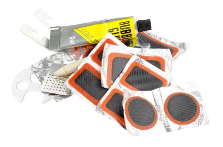 puncture: Contents of a bicycle tyre puncture repair kit including patches and rubber glue isolated on a white background