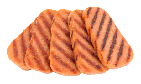 Slices of fried Spam pork luncheon meat isolated on a white background