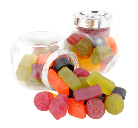 spilling: Two jars of traditional wine gum sweets one tipped over with sweets spilling out isolated on a white background