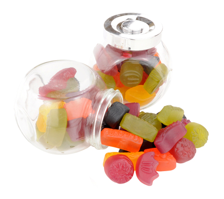 tipped: Two jars of traditional wine gum sweets one tipped over with sweets spilling out isolated on a white background