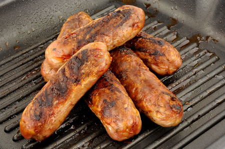 non stick: Freshly cooked pork sausages in a non stick griddle frying pan