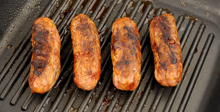ridged: Freshly cooked pork sausages in a non stick griddle frying pan