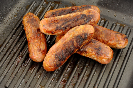griddle: Freshly cooked pork sausages in a non stick griddle frying pan