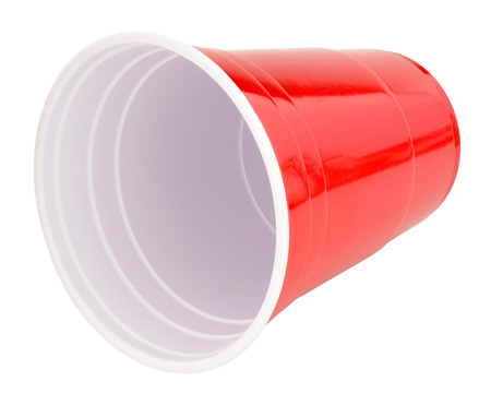 toppled: Single disposable red plastic drinking cup isolated on a white background Stock Photo