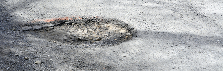 Dangerous pothole in a damaged tarmac road surface