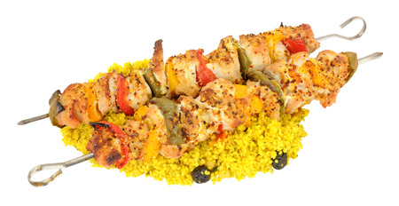Grilled chicken and sweet pepper kebabs on metal skewers with couscous isolated on a white background Stock Photo