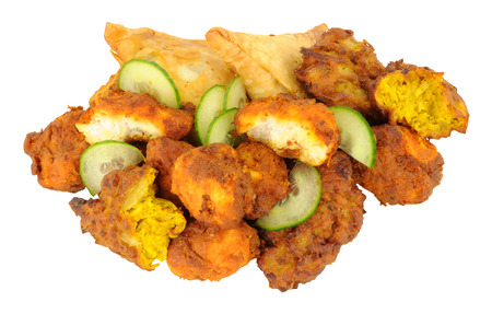 Fried Indian snacks including, samosas, onion bhajis and pakoras isolated on a white background Stock Photo