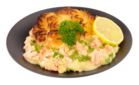 fish isolated: Portion of crispy potato topped fish pie on a black plate isolated on a white background