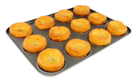 Twelve freshly baked Yorkshire puddings in a non stick baking tray Stock Photo