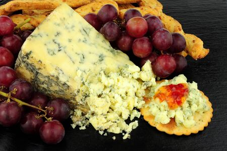 stilton: Blue veined strong English Stilton cheese wedge and red grapes on a stone slate background