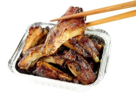 hoisin: Hoisin sauce Chinese pork ribs in a foil take away tray isolated on a white background