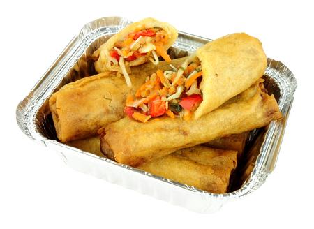 Chinese crispy vegetable filled spring rolls in an aluminium foil take away tray isolated on a white background