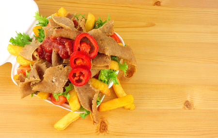 Doner kebab meat and chips with salad and chilli sauce in a take away tray on a wood background Stock Photo
