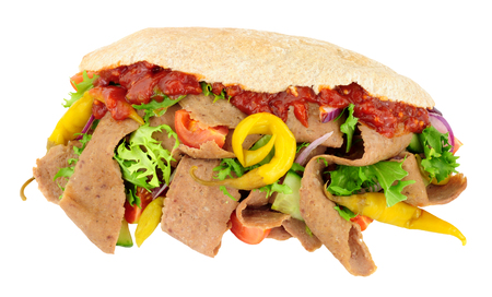 Doner kebab meat and fresh salad in a pitta bread isolated on a white background