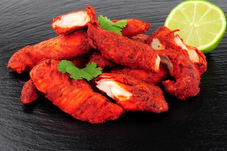 Group of tandoori chicken on a slate background