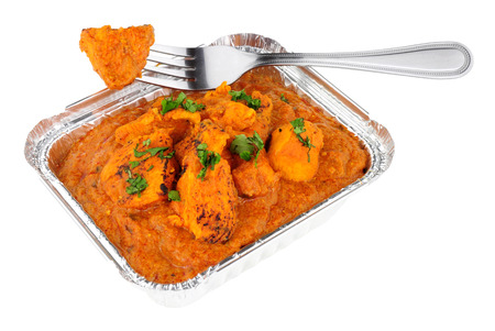 Creamy chicken tikka masala curry in a foil take away tray isolated on a white background Archivio Fotografico