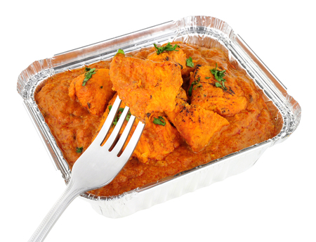 Creamy chicken tikka masala curry in a foil take away tray isolated on a white background Stock Photo