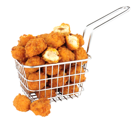 Fried breadcrumb covered chicken popcorn in a small wire frying basket isolated on a white background