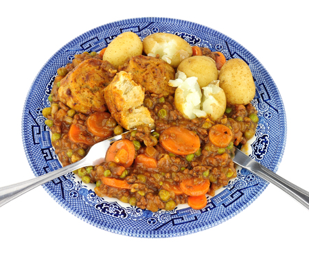 Minced beef stew with dumplings and new potatoes on a blue patterned plate isolated on a white background