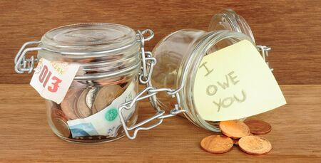Glass jars filled with cash savings on a wood background Banco de Imagens - 81592537